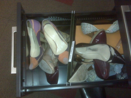 This is the bottom drawer of my desk.  FULL OF SHOES!  This started at my old job, when I never knew if heels, flats, sneakers, galoshes or snow shoes would be appropriate.  Instead of lugging all of them back and forth from home, I'd keep them in my desk drawer.  BTW: Those Jimmy Choos have black lines through them because they're irregulars I got on eBay!